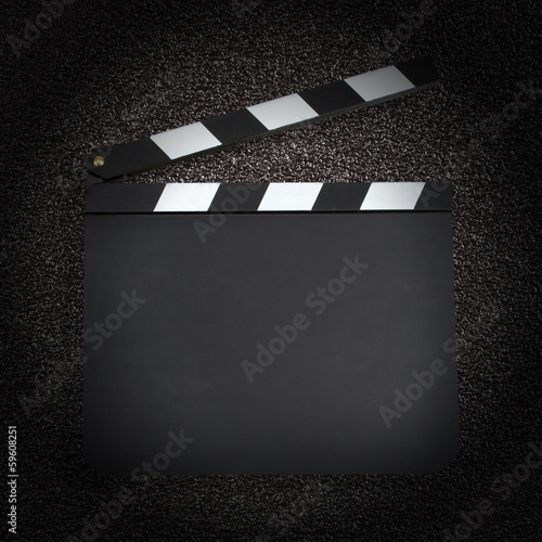 Blank movie production clapper board over dark background