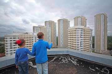 Two children stand on the roof of the apartment building