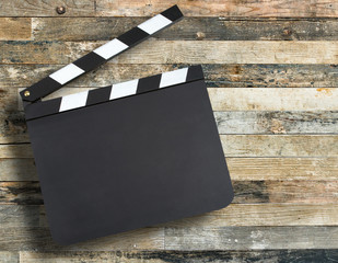 Blank movie production clapper board over wooden background