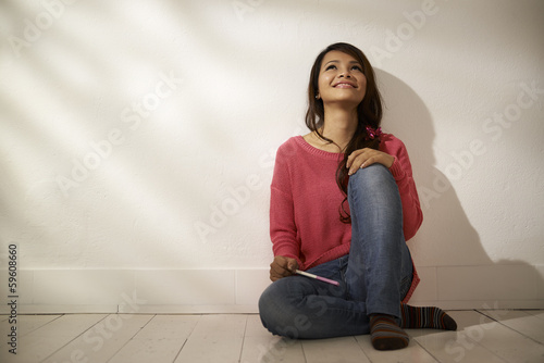Happy Asian girl holding pregnancy test at home
