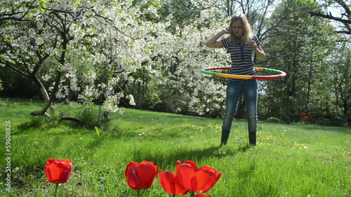 woman turn hula hoop ring on waist in beautiful spring garden