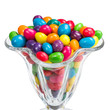 Transparent glass full of sweet colorful candy against white