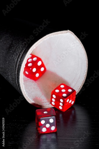 red dice on old wood black table near a container