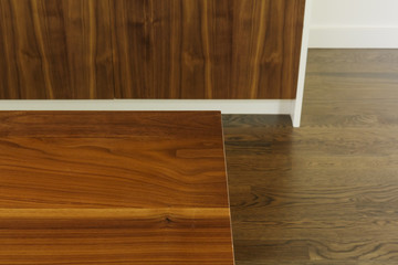 Detail of wood dining table grain against floor and cabinet