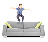 Little boy jumping on a sofa