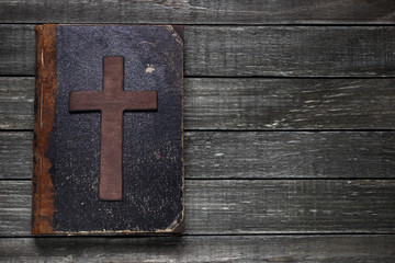 Old book and cross on wooden table
