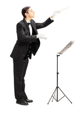 Full length portrait of a male orchestra conductor directing