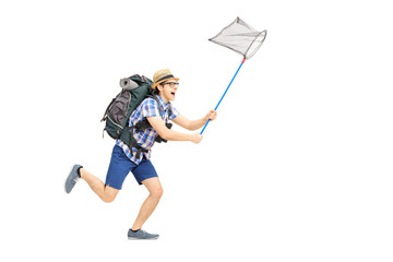Full length portrait of male tourist running with butterfly net