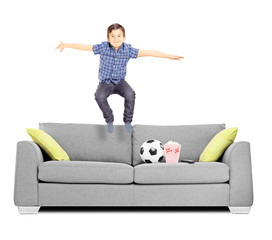 Happy little boy jumping on a sofa
