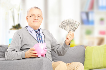Senior gentleman on sofa holding a piggy bank and money at home