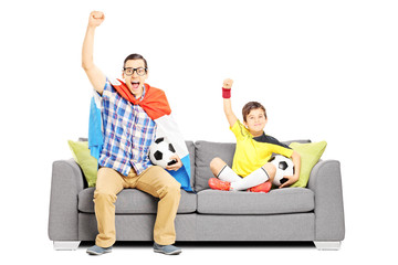 Two male sport fans seated on a sofa watching sport
