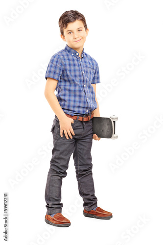 Full length portrait of a cute young boy holding a skateboard
