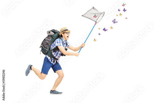 Full length portrait of a male tourist catching butterflies