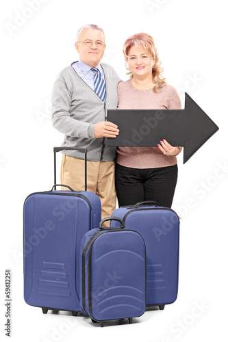 Smiling mature tourists holding a big black arrow and travel bag