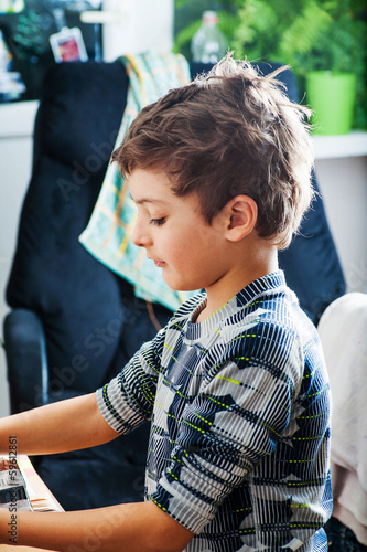 Side view of a little boy at table in the room