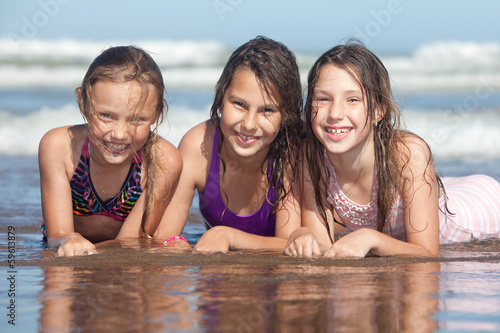 three happy girls on the beach