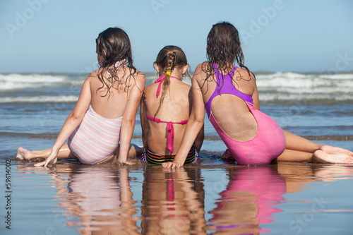 three girls sitting on the beach