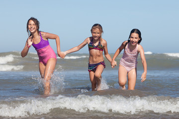 three happy girls running out of ocean