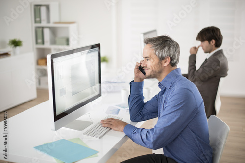businessman at phone watching his computer