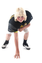 Young blond American football player boy in stance