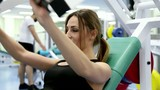 Young woman trains at a gym (on the simulator)