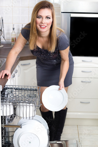 sexy housewife takes out the plates from the dishwasher