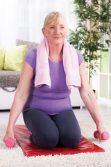 senior woman sitting on a mat at home and exercise with weights