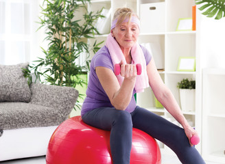 happy senior woman sitting on gym ball, and exercise with dumbbe