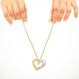 Male hands holding a gold chain with pendant-heart with gems