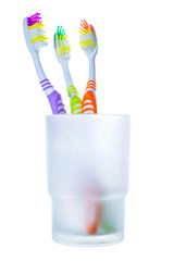 Three colorful toothbrushes in glass