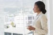 Elegant businesswoman with tea cup looking through office window