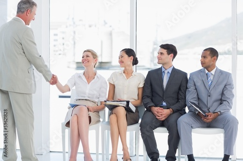 Businessman shaking hands with woman by people waiting for inter