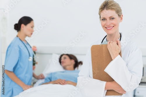 Smiling doctor with patient in hospital