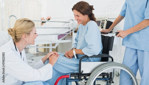 Doctor talking to patient in wheelchair at hospital