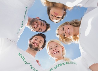 Happy volunteers forming a huddle against blue sky