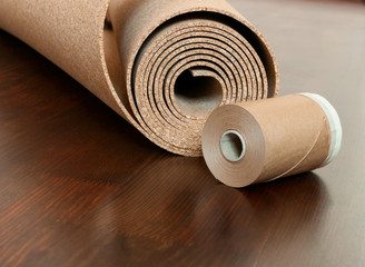 Roll of cork with Painting edging tape on a brown floor
