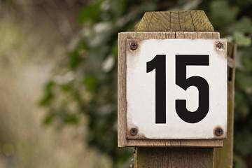 Hausnummer 15 an einem Holzpfosten