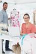 Woman using laptop with fashion designer working at studio