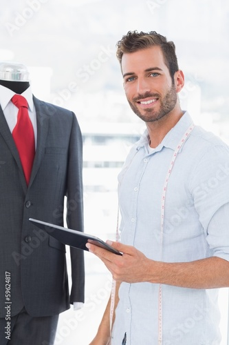 Fashion designer with digital tablet by suit on dummy