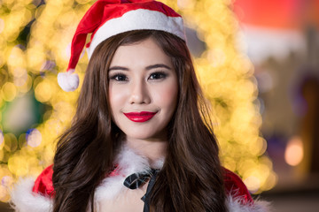 Pretty Asian girl in Santa costume for Christmas with night ligh