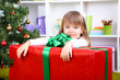 Little girl with big present box near Christmas tree in room