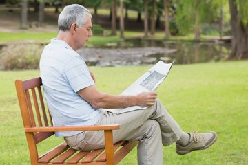 Relaxed senior man reading newspaper at park