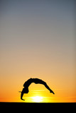 silhouette of female gymnast in sunset