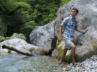 young man standing near rock in mountain forest