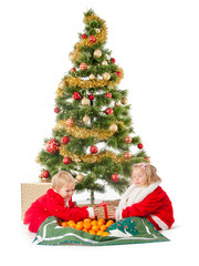 two little children playing  under christmas tree