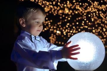 boy holding a glowing ball.