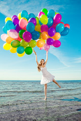 Beautiful young stylish woman with multi-colored rainbow balloon