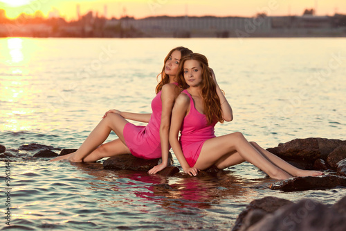 Two beauty women on the beach at sunset. Enjoy nature. Luxury gi
