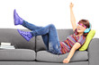 Young excited female listening music seated on a couch