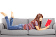 Young female lying on a sofa and reading a book